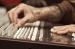 Closeup of hands covered with tattoos working on mixer console, twisting knobs, studio equipment concept Royalty Free Stock Photos