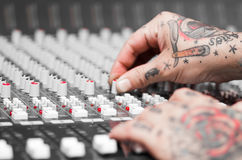 Closeup of hands covered with tattoos working on mixer console, twisting knobs, studio equipment concept Stock Photos