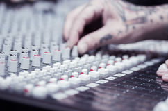 Closeup of hands covered with tattoos working on mixer console, twisting knobs, studio equipment concept Royalty Free Stock Image