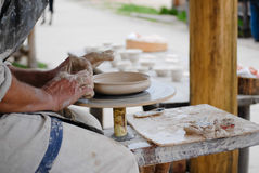 Closeup on hands of craftsman making vase from fresh wet clay on pottery wheel Royalty Free Stock Photography