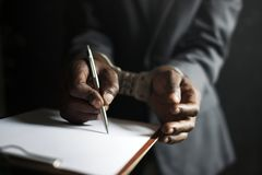 Closeup of hands cuffed forced to sign paper Royalty Free Stock Photography
