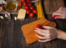 Closeup of hands cutting tomatoes for spaghetti stock photography