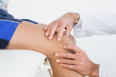 Closeup of hands examining patients knee Royalty Free Stock Images