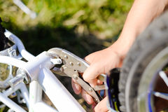 Closeup on hands of father fixing mechanism of the bicycle, green background outside Stock Images