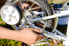 Closeup on hands of father fixing mechanism of the bicycle, green background outside Royalty Free Stock Images
