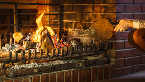 Closeup hands fireplace making fire with bellows. Stock Photos