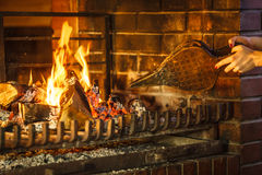Closeup hands fireplace making fire with bellows. Royalty Free Stock Photos