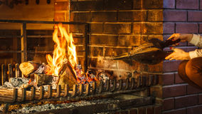 Closeup hands fireplace making fire with bellows. Stock Images