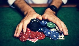 Closeup of hands with gambling tokens and card royalty free stock image