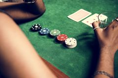 Closeup of hands with gambling tokens and card stock photo