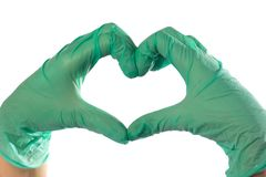 Closeup of hands in green latex gloves. The heart is folded from the hands stock photography