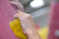 Closeup hands gripping on to indoor climbing wall support Stock Photography