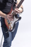 Closeup of Hands and Guitar of Caucasian Musician. Posing Agains. T White. Vertical Image stock photography
