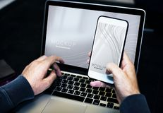 Person Using Smartphone While Facing Laptop Computer royalty free stock image