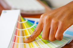 Closeup hands holding palette, colormap spread out in front of white computer keyboard, designer concept.  stock photos