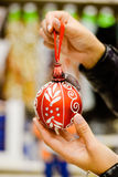 Closeup of hands holding red ornament ball painted Royalty Free Stock Photography