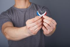 Closeup of hands holding small inconspicuous hearing aids in heart shape royalty free stock photo