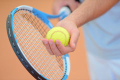 Closeup hands holding tennis racket and ball poised to serve Stock Photo