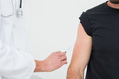 Closeup of hands injecting a young male patients arm Royalty Free Stock Images