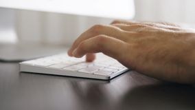 Close up of male hands typing on keyboard in the office stock video