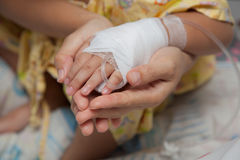 Closeup of hands of a little Boy attaching intravenous tube to patient`s hand in hospital bed, And the hands of mother with love. stock images