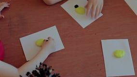 Closeup hands little girl modelling plasticine. Child molds a ladybug from plasticine. Close up stock video