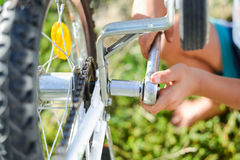 Closeup on hands of male fixing mechanism of the bicycle, green background outside Royalty Free Stock Photo