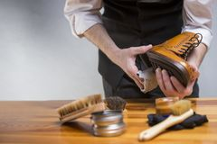 Closeup of hands of man cleaning premium derby boots Stock Image