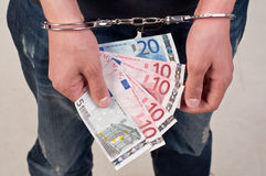 Closeup of hands man in handcuffs holding money Royalty Free Stock Images