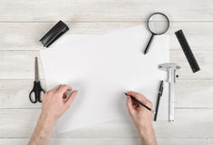 Closeup hands of man holding pencil and drawing on white paper in top view. Draftsman workplace equipped with ruler, pen. Closeup hands of man holding pencil and Stock Photos