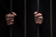Closeup on hands of man sitting in jail. Stock Photo