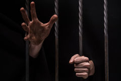 Closeup on hands of man sitting in jail. Royalty Free Stock Image