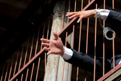 Closeup on hands of man sitting in jail royalty free stock photo