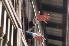 Closeup on hands of man sitting in jail. Man behind jail bars on black background reaching Royalty Free Stock Image