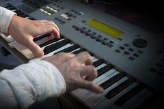 Closeup hands of musician playing synthesizer in concert. Half vignetted image royalty free stock images