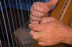 Closeup Hands Playing Harp. This photo shows a pair of hands closeup playing a stringed harp Royalty Free Stock Photo