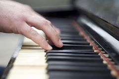 Closeup of hands playing piano. Closeup shot of male hands on the piano keyboard royalty free stock image