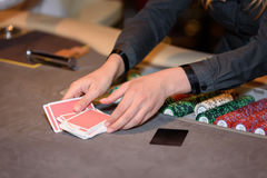 Closeup of hands of poker croupier with chips and cards in casin. O Stock Photo