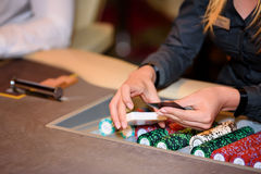 Closeup of hands of poker dealer with chips and cards in casino,. Closeup of hands of poker dealer with chips and cards in casino Royalty Free Stock Image