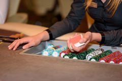 Closeup of hands of poker dealer with chips in casino, selective Stock Images