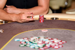 Closeup of hands of poker player with chips on poker table, sele Stock Photo