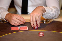 Closeup of hands of poker player with chips on poker table, sele Royalty Free Stock Images