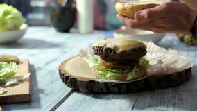 Closeup of hands preparing cheeseburger.