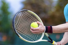 Closeup of Hands of Professional Male tennis Player Holding Raqu. Et and Tennis Ball in Contact. Horizontal Image Composition royalty free stock images