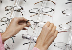 Closeup Of Hands Pulling Glasses From Display Rack. Closeup of a female's hands pulling glasses from display rack Royalty Free Stock Images