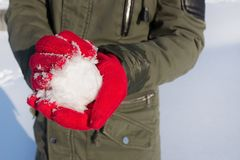 Hands in red gloves holding snowball. Closeup of hands in red gloves holding snowball in winter outdoors stock photo