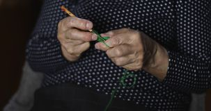 Closeup of the hands of a senior woman knitting with green threads. Hobby stock video footage