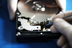 Closeup of hands with tweezers and computer hard disk Royalty Free Stock Photos