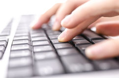 Closeup of hands typing on computer keyboard. With shallow depth of field stock photo