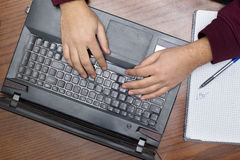 Closeup on Hands Typing on Keyboard, Notebook and Pen. Closeup on Hands Typing on Keyboard, Paper Note and Pen, and Arabic Word Written `Ideas stock photography